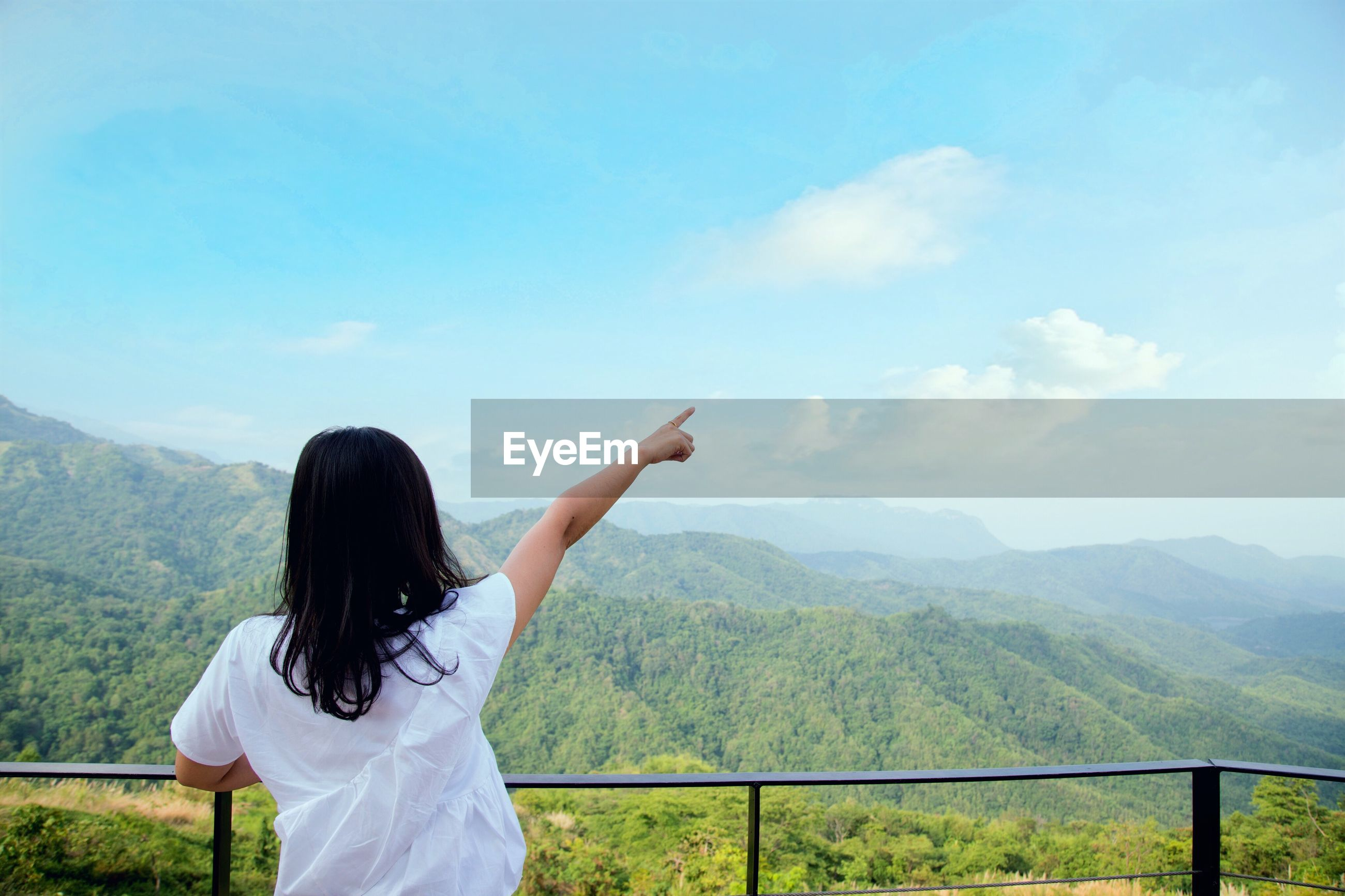 Rear view of woman pointing at mountains against sky
