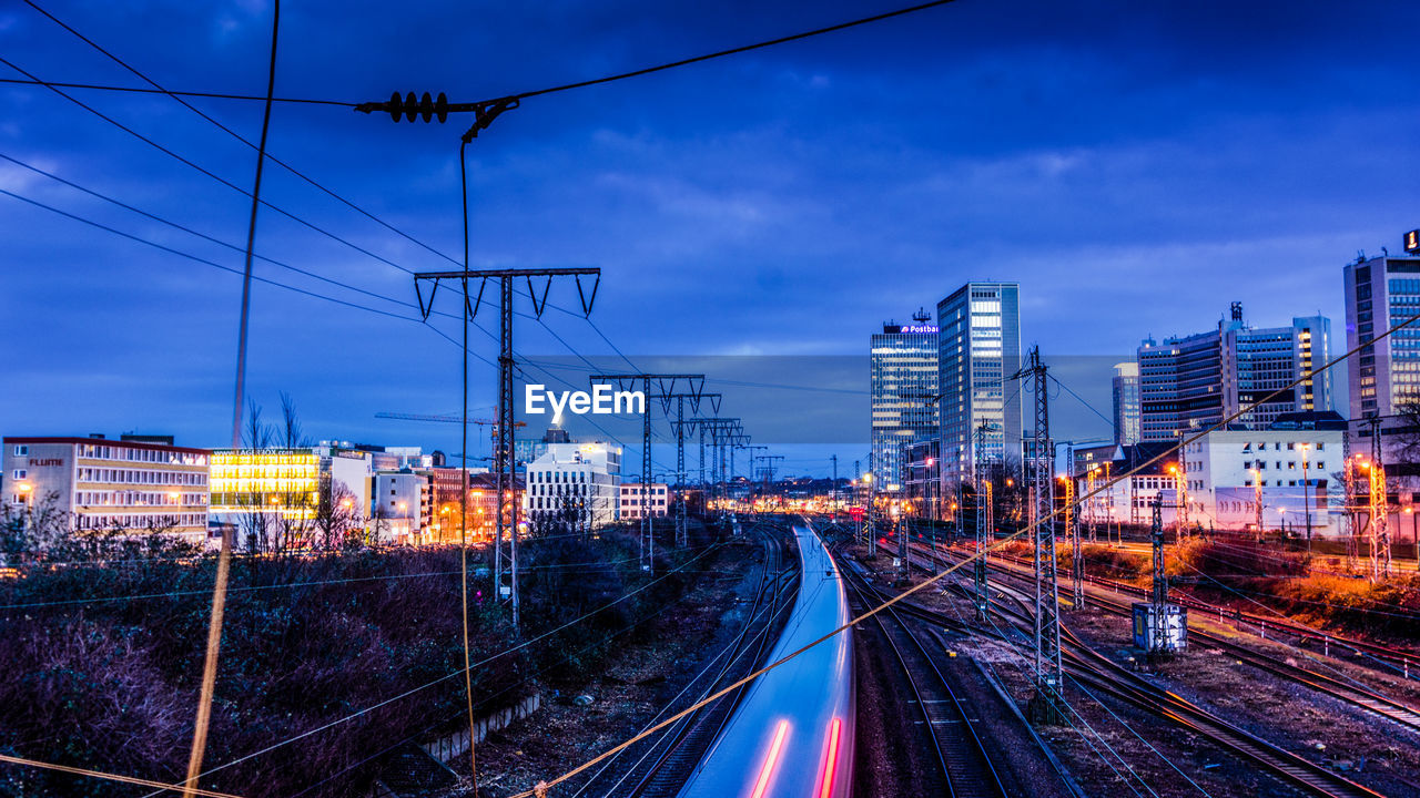 railroad track, sky, track, rail transportation, architecture, transportation, illuminated, building exterior, cloud - sky, city, built structure, dusk, nature, no people, mode of transportation, electricity, public transportation, technology, cable, motion, outdoors, complexity, office building exterior, power supply