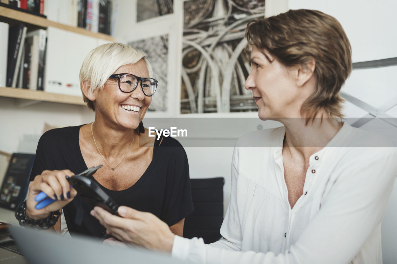 smiling, two people, mature adult, women, adult, mature women, indoors, females, real people, glasses, happiness, emotion, people, business, eyeglasses, front view, businesswoman, business person, headshot, hairstyle, coworker
