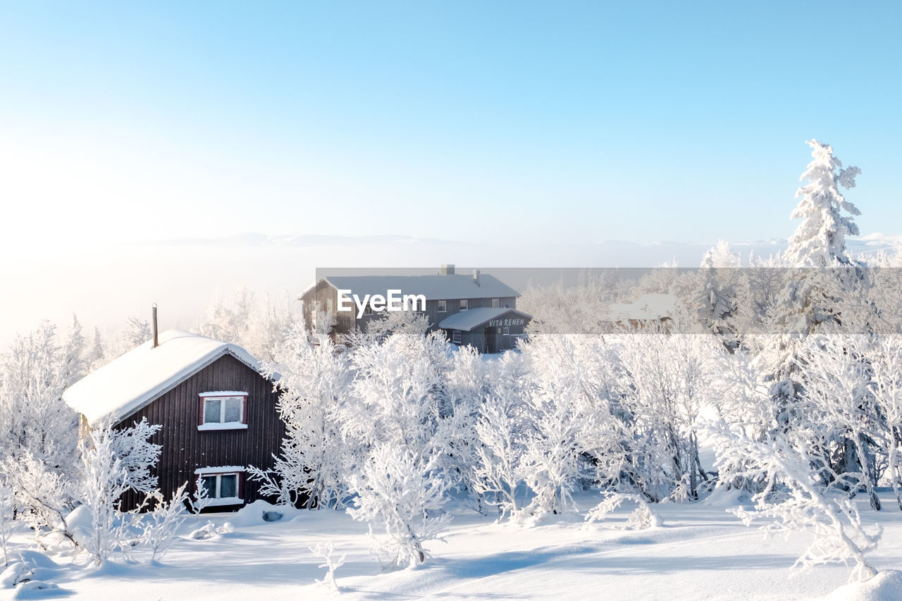 snow, winter, cold temperature, house, built structure, building exterior, architecture, white color, nature, white, beauty in nature, no people, outdoors, tranquil scene, tranquility, frozen, tree, scenics, landscape, day, clear sky, blue, sky