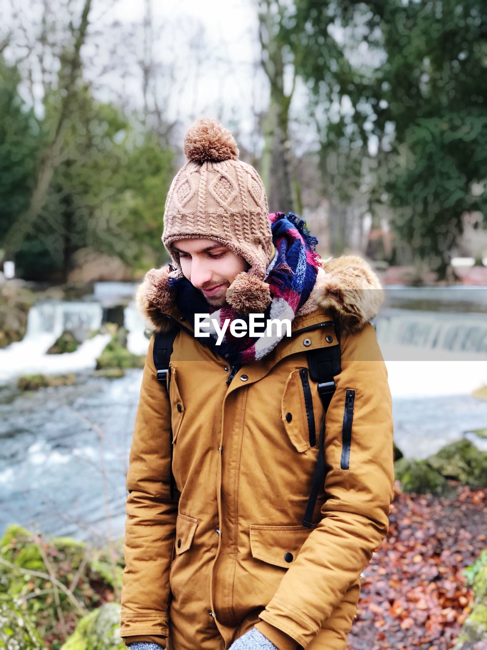 Smiling young man standing with river in background during winter