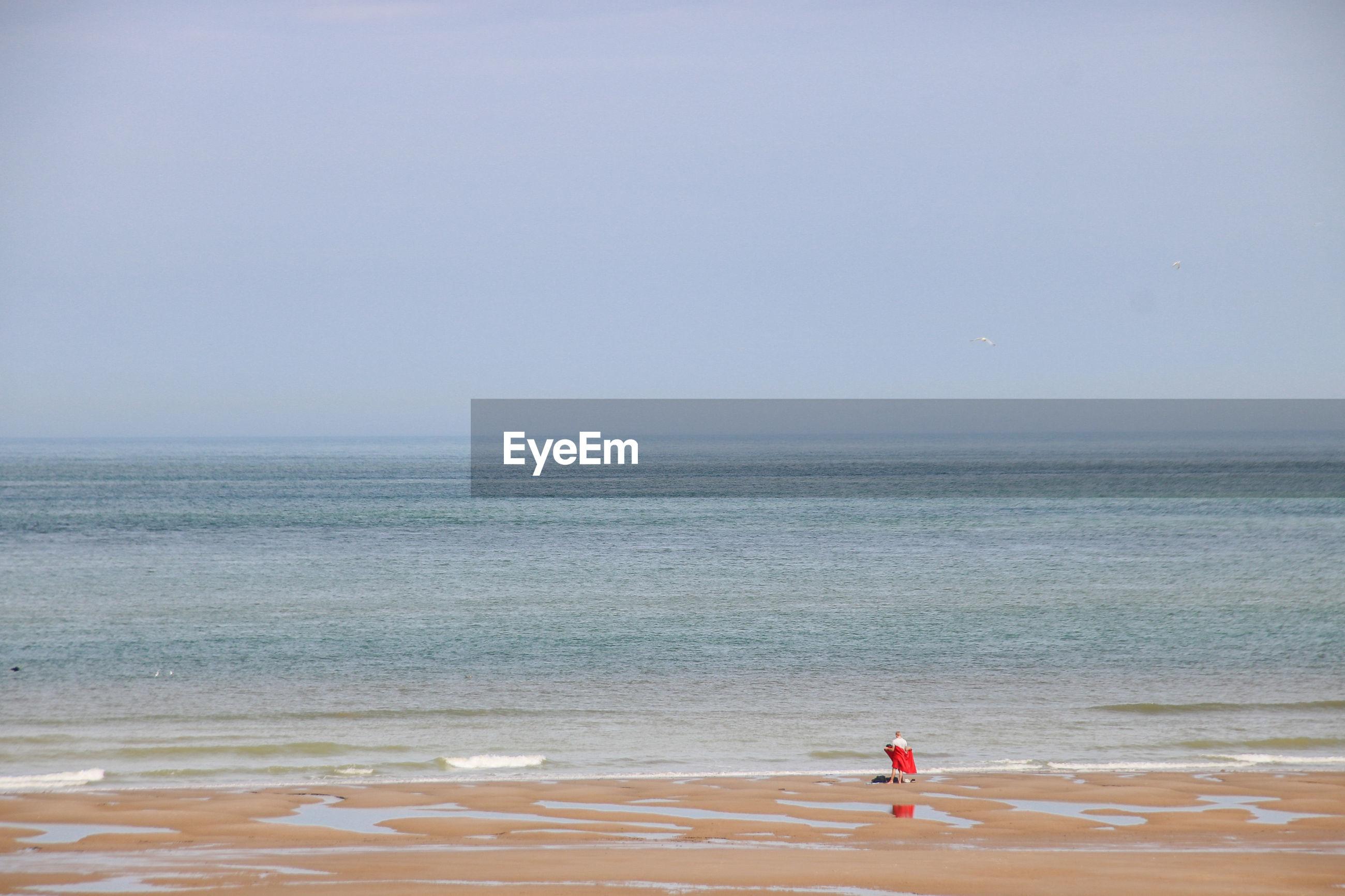 PERSON ON BEACH AGAINST SKY