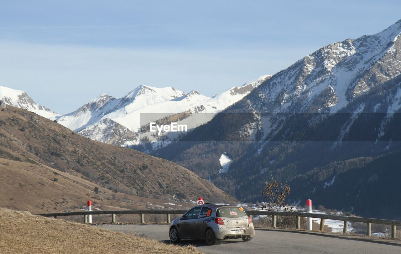 CARS ON ROAD BY SNOWCAPPED MOUNTAIN AGAINST SKY