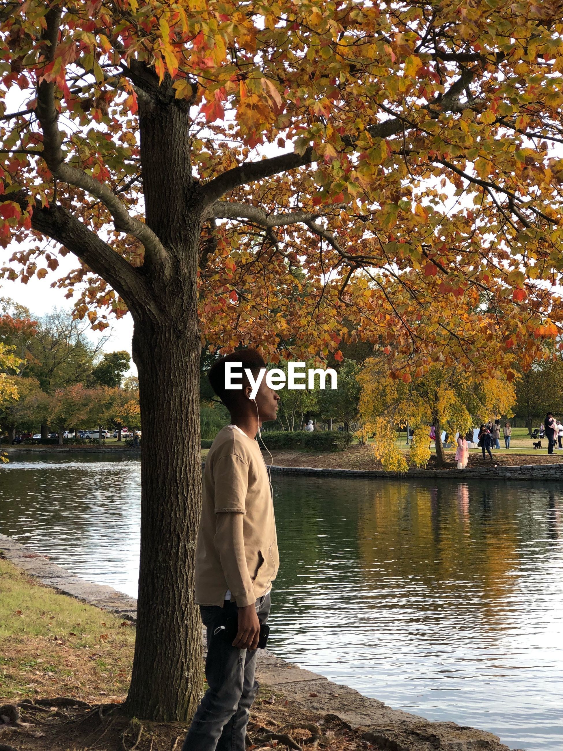 Boy standing by lake during autumn