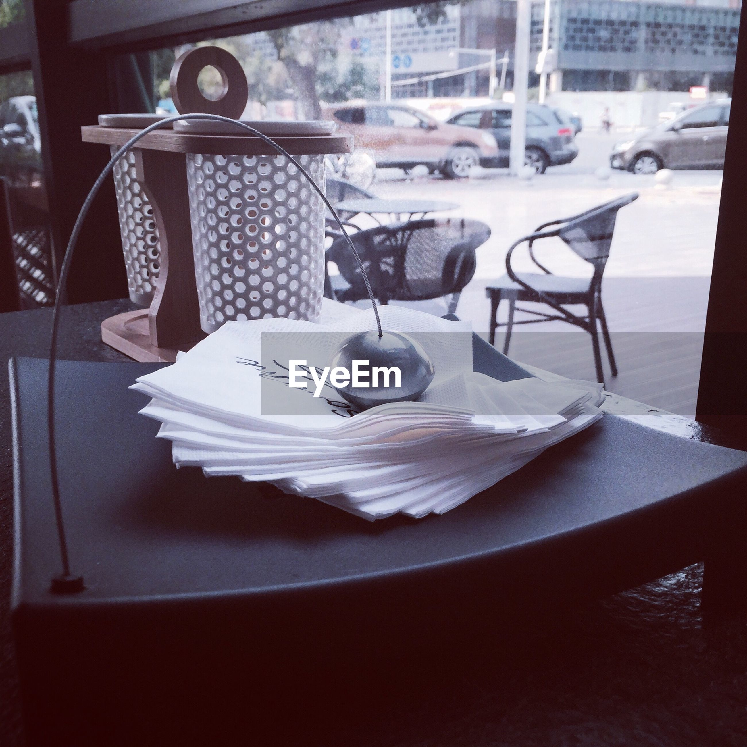 table, indoors, bird, chair, water, animal themes, restaurant, day, no people, white color, absence, glass - material, empty, reflection, still life, high angle view, sunlight, focus on foreground, close-up