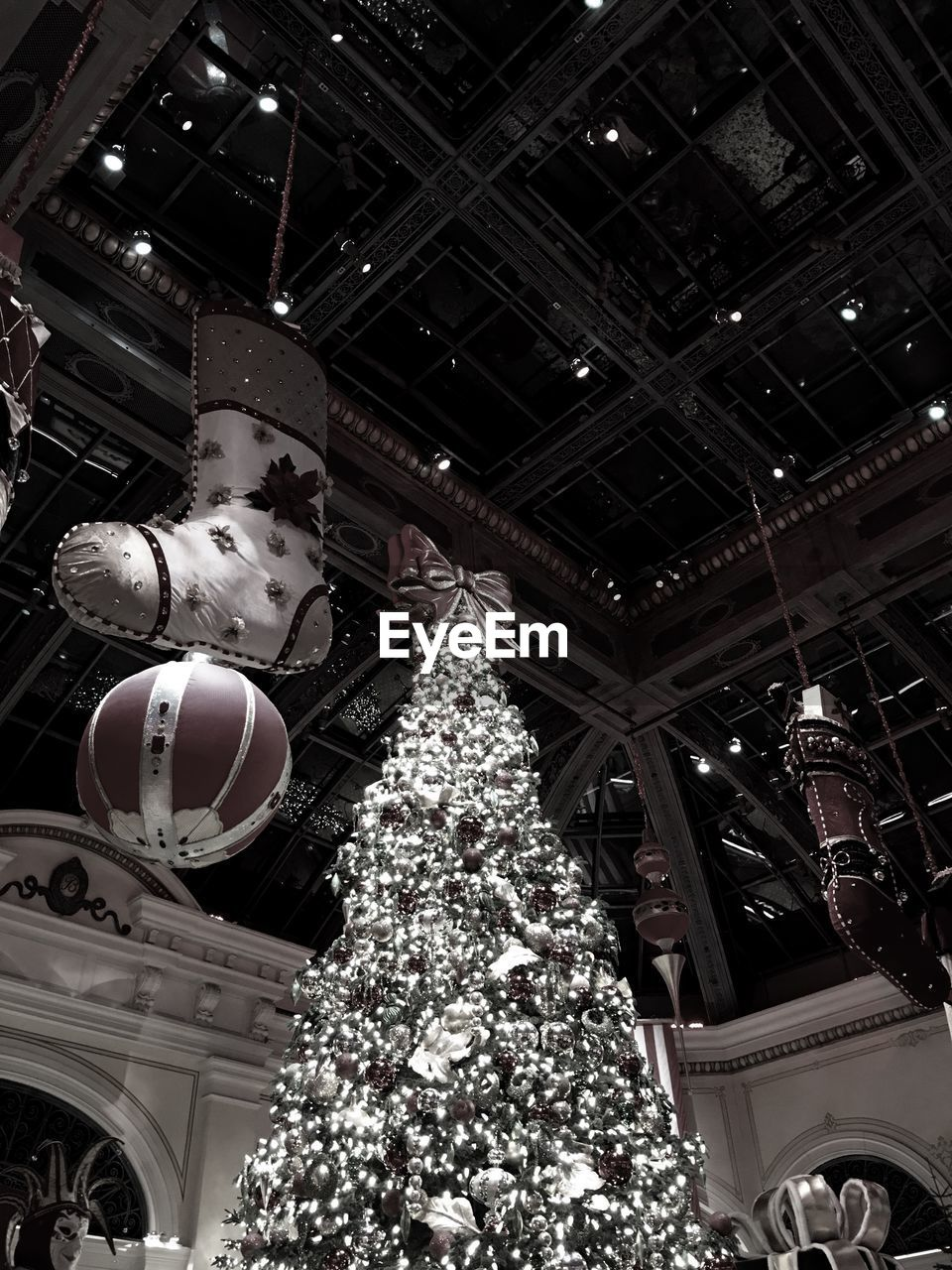 christmas, low angle view, ceiling, celebration, christmas decoration, christmas tree, indoors, hanging, christmas ornament, no people, illuminated, architecture, night, tree