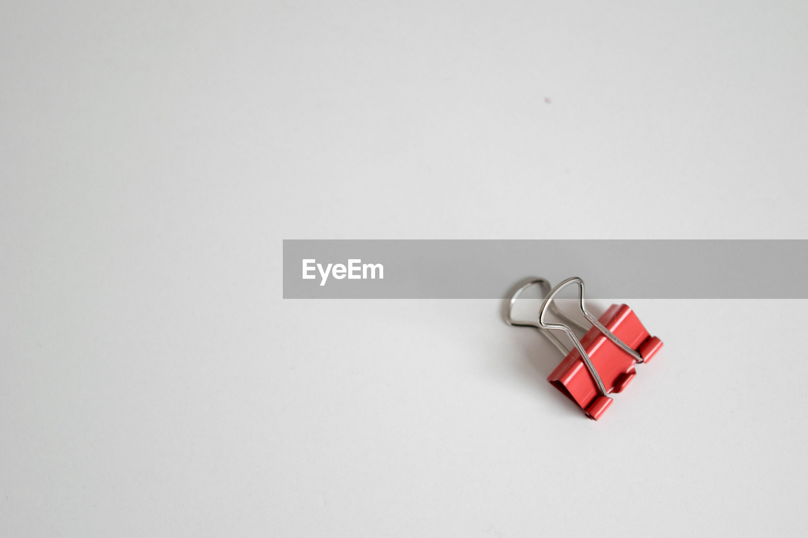 Close-up of red metal clip over white background