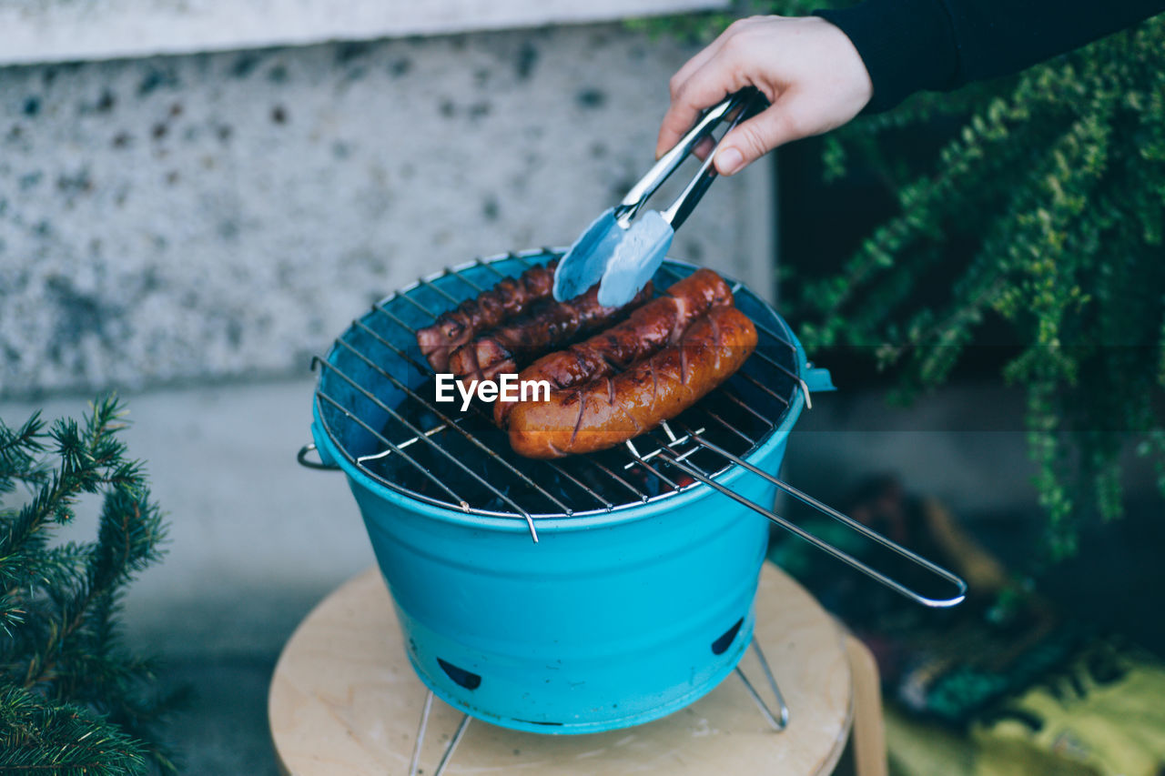 Close-Up Of Person Preparing Food On Barbecue