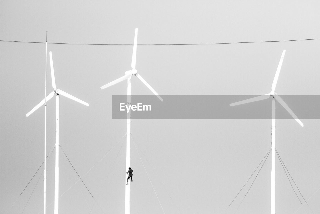 Low Angle View Of Person Climbing On Wind Turbine