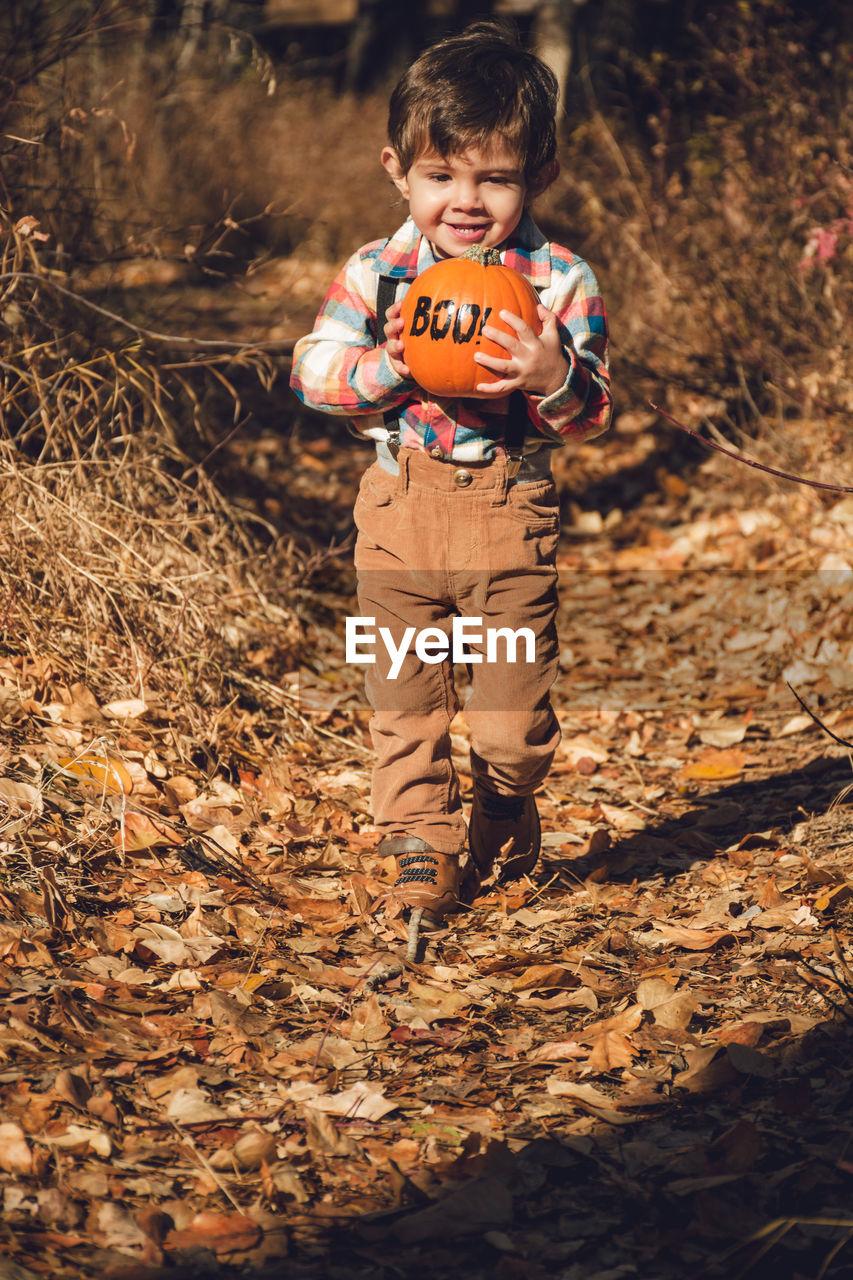 Portrait Of Boy Holding Pumpkin While Walking On Field