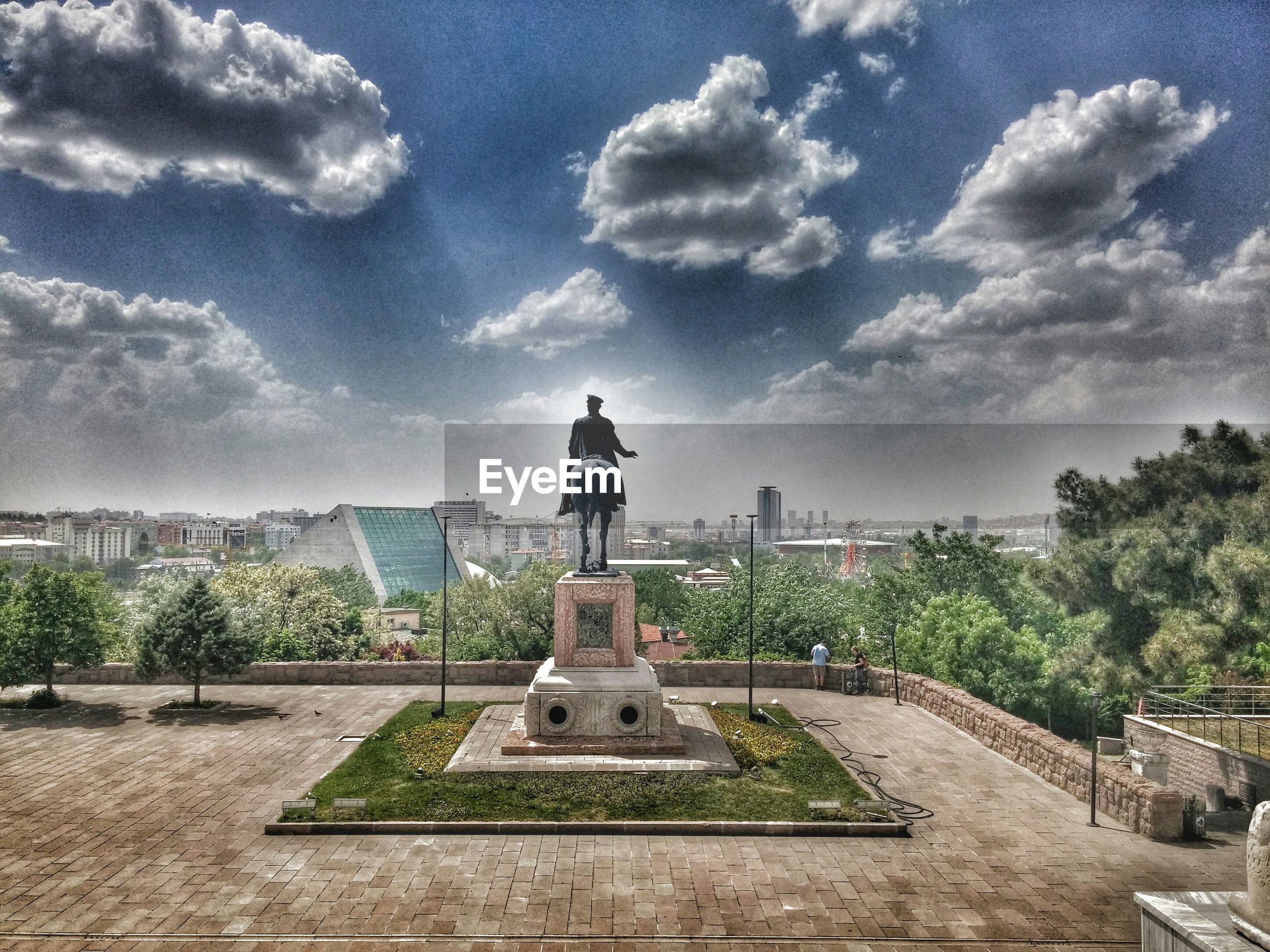 building exterior, architecture, built structure, sky, tree, cloud - sky, city, cloud, blue, cityscape, day, residential building, statue, sculpture, sunlight, outdoors, tower, human representation, no people, residential structure