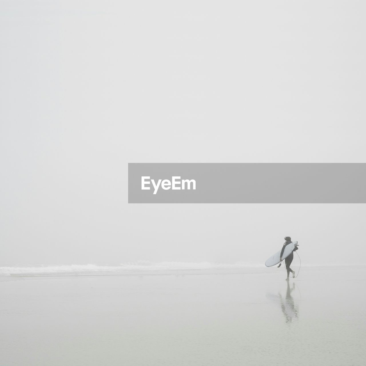 Person With Surfboard At Sea Shore Against Sky During Foggy Weather