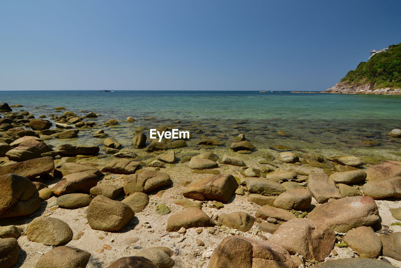 water, sky, sea, beauty in nature, horizon, scenics - nature, horizon over water, tranquility, beach, clear sky, land, tranquil scene, nature, rock, no people, solid, copy space, rock - object, day, shallow, pebble, turquoise colored