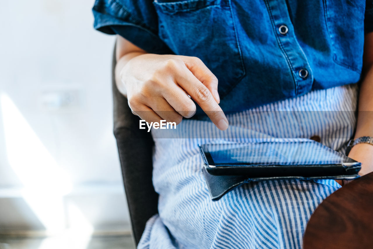 Midsection of woman using digital tablet