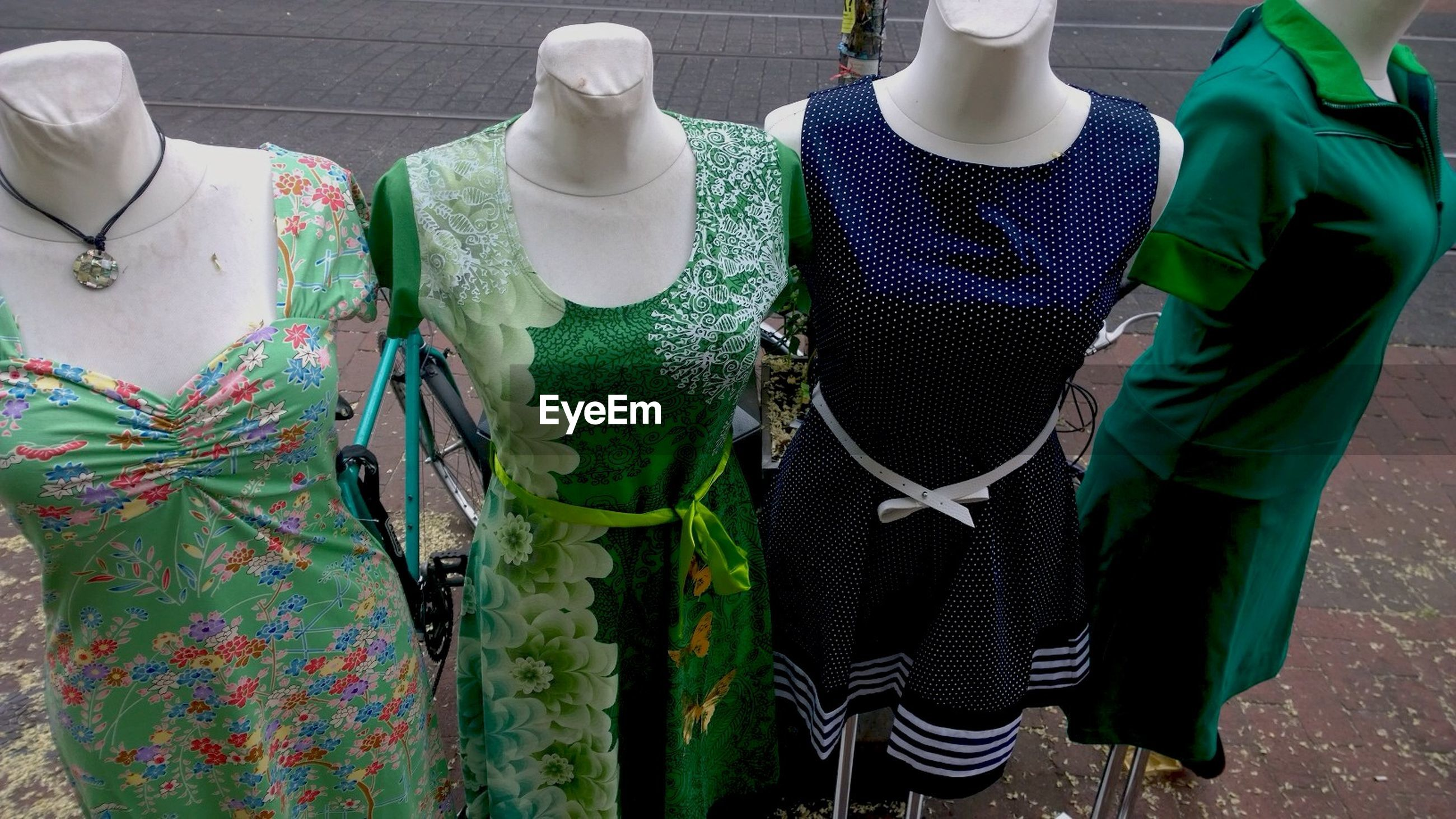 Various dresses on mannequins against street