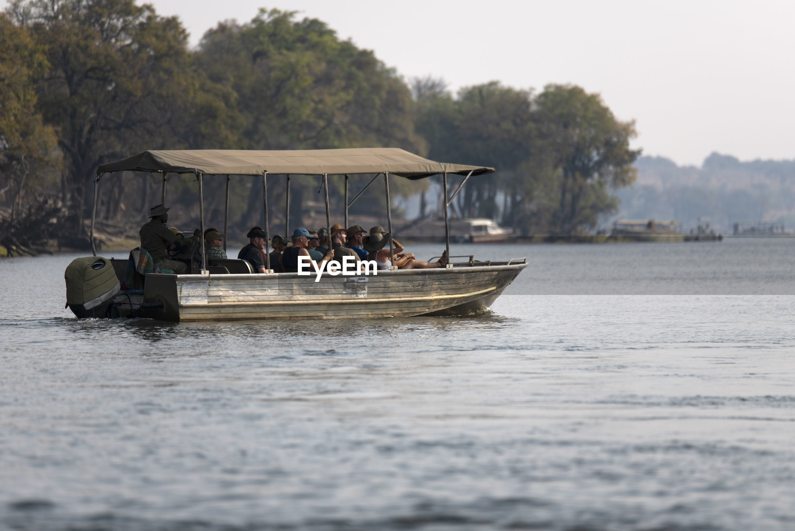 People sitting in boat in river against trees