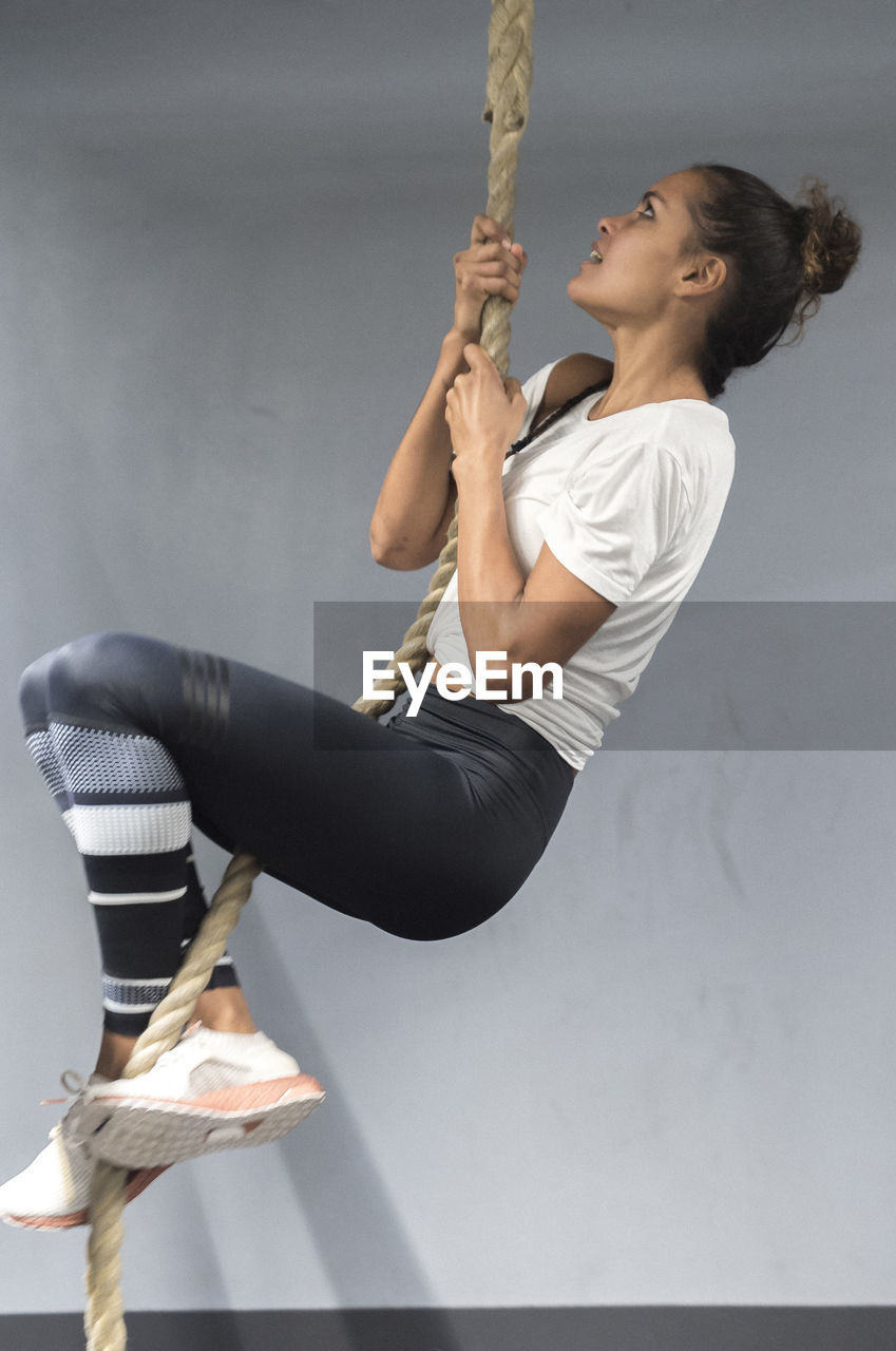 one person, sport, holding, full length, lifestyles, indoors, exercising, healthy lifestyle, vitality, strength, young adult, young women, side view, real people, skill, wellbeing, sports clothing, athlete, determination