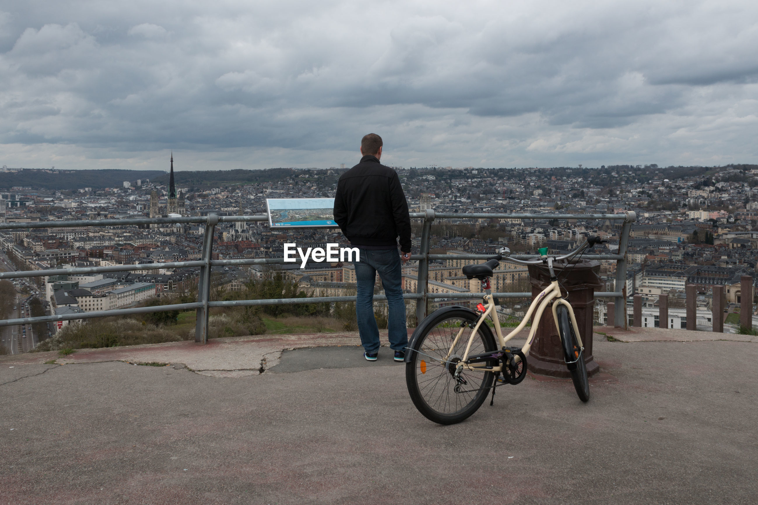 MAN WITH BICYCLE IN CITY AGAINST SKY
