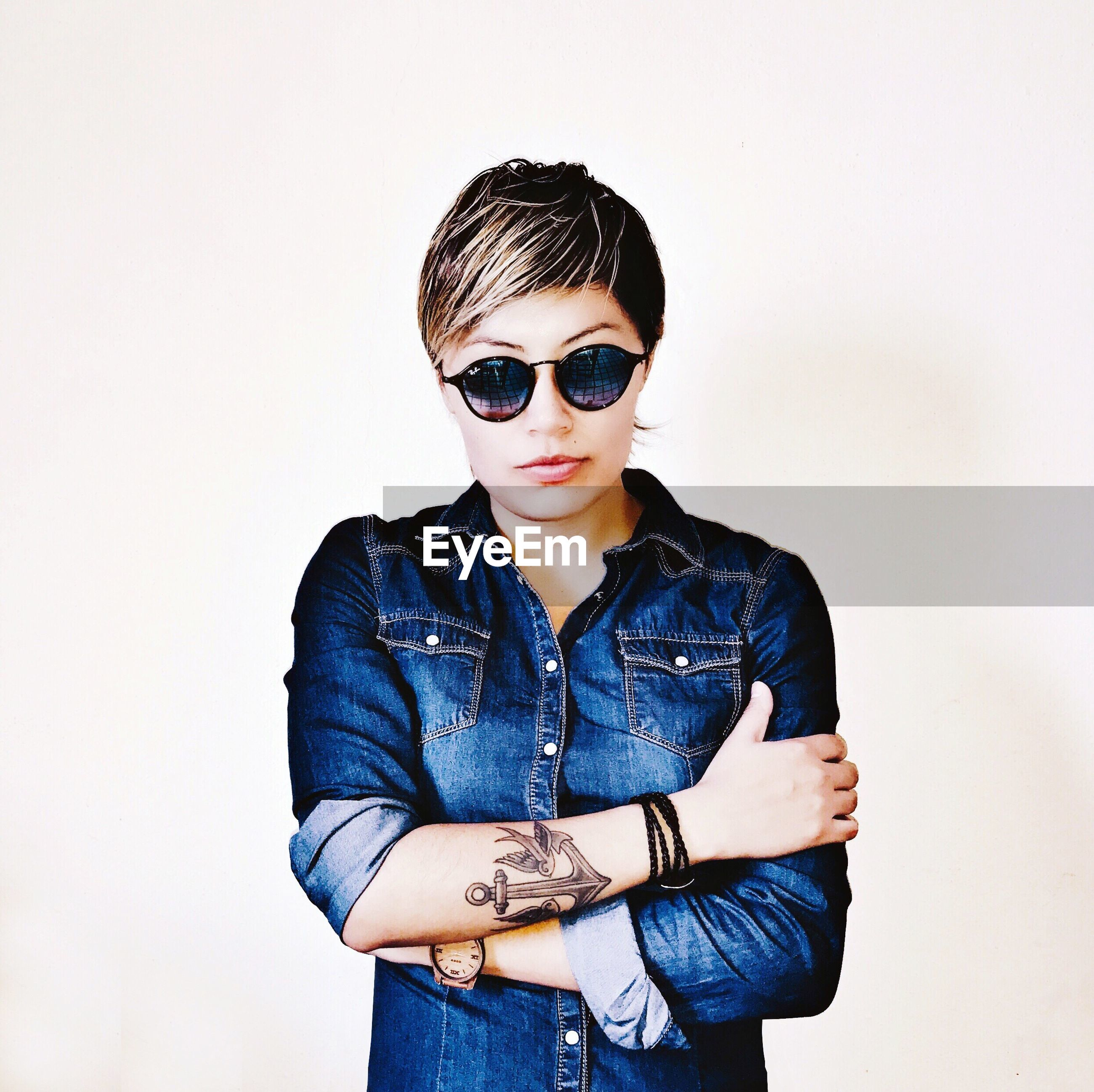 PORTRAIT OF BEAUTIFUL YOUNG WOMAN WEARING SUNGLASSES AGAINST WHITE BACKGROUND