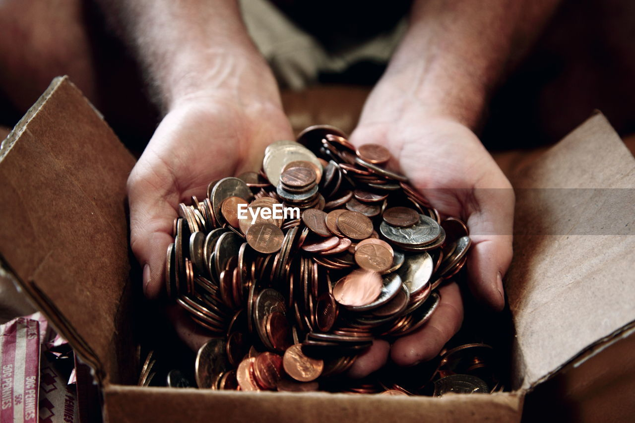 Close-Up Of Man Putting Us Coins In Cardboard Box