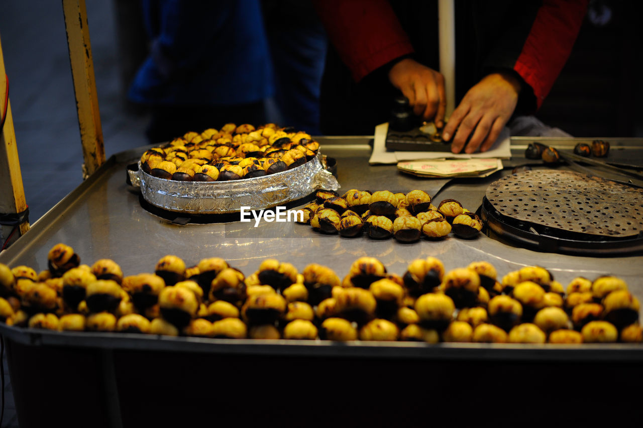 Midsection Of Vendor Preparing Food At Market Stall