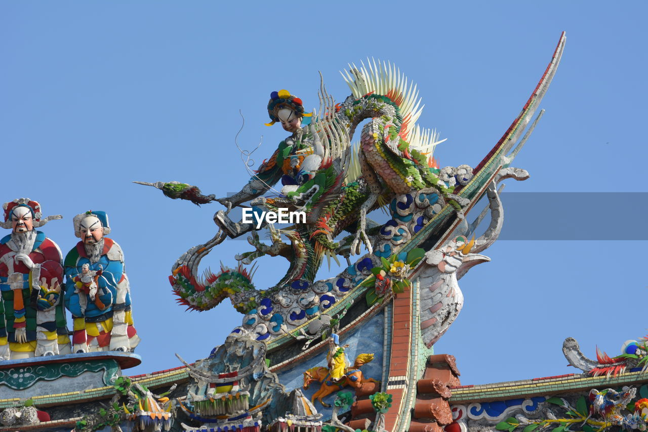 statue, sculpture, low angle view, art and craft, human representation, creativity, clear sky, male likeness, day, blue, spirituality, religion, outdoors, built structure, architecture, sunlight, sky, dragon, building exterior, place of worship, no people, travel destinations, multi colored, chinese dragon