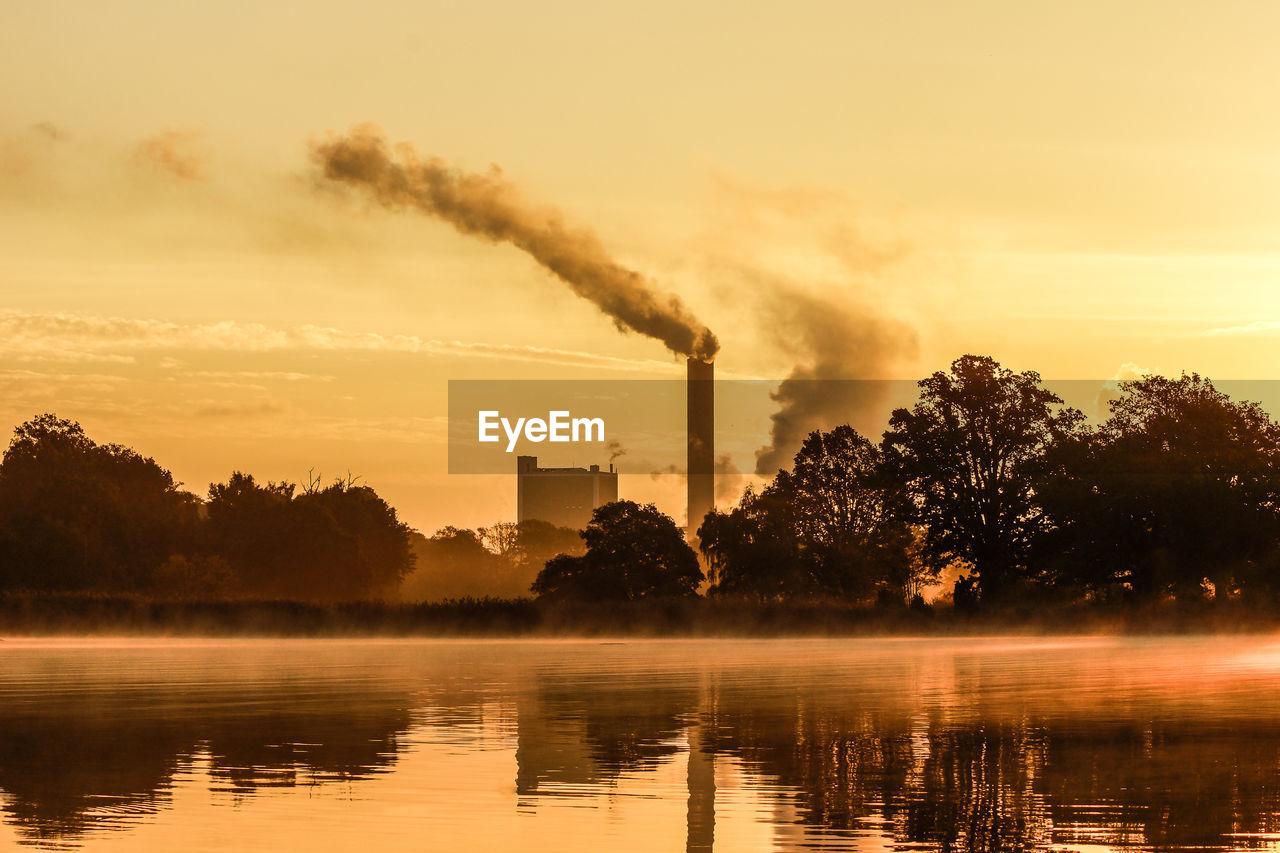 Smoke Emitting From Smoke Stack By Lake