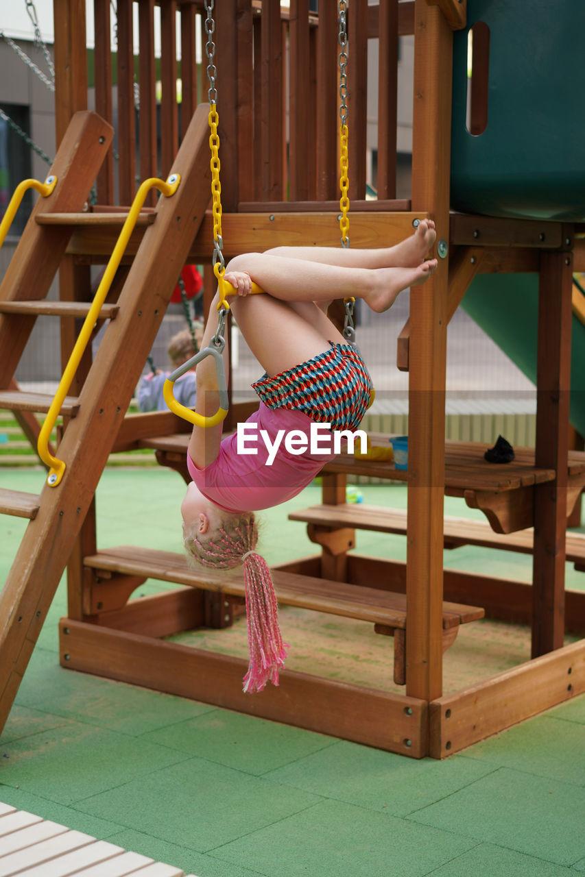 Full length of girl hanging upside down on swing at park