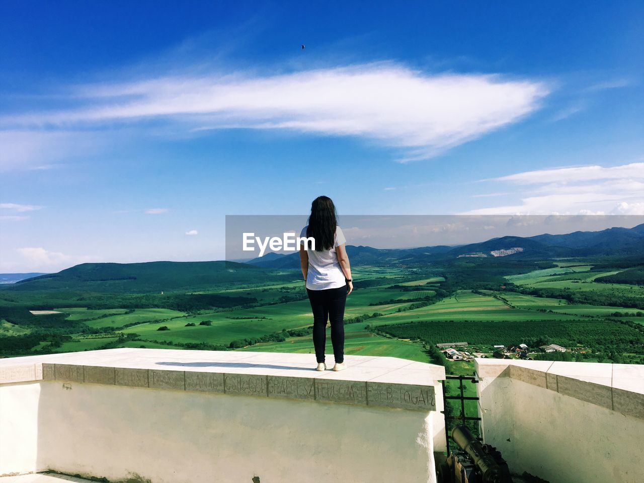 one person, sky, standing, cloud - sky, mountain, real people, lifestyles, beauty in nature, rear view, scenics - nature, leisure activity, nature, women, day, full length, adult, casual clothing, landscape, environment, outdoors, hairstyle, looking at view