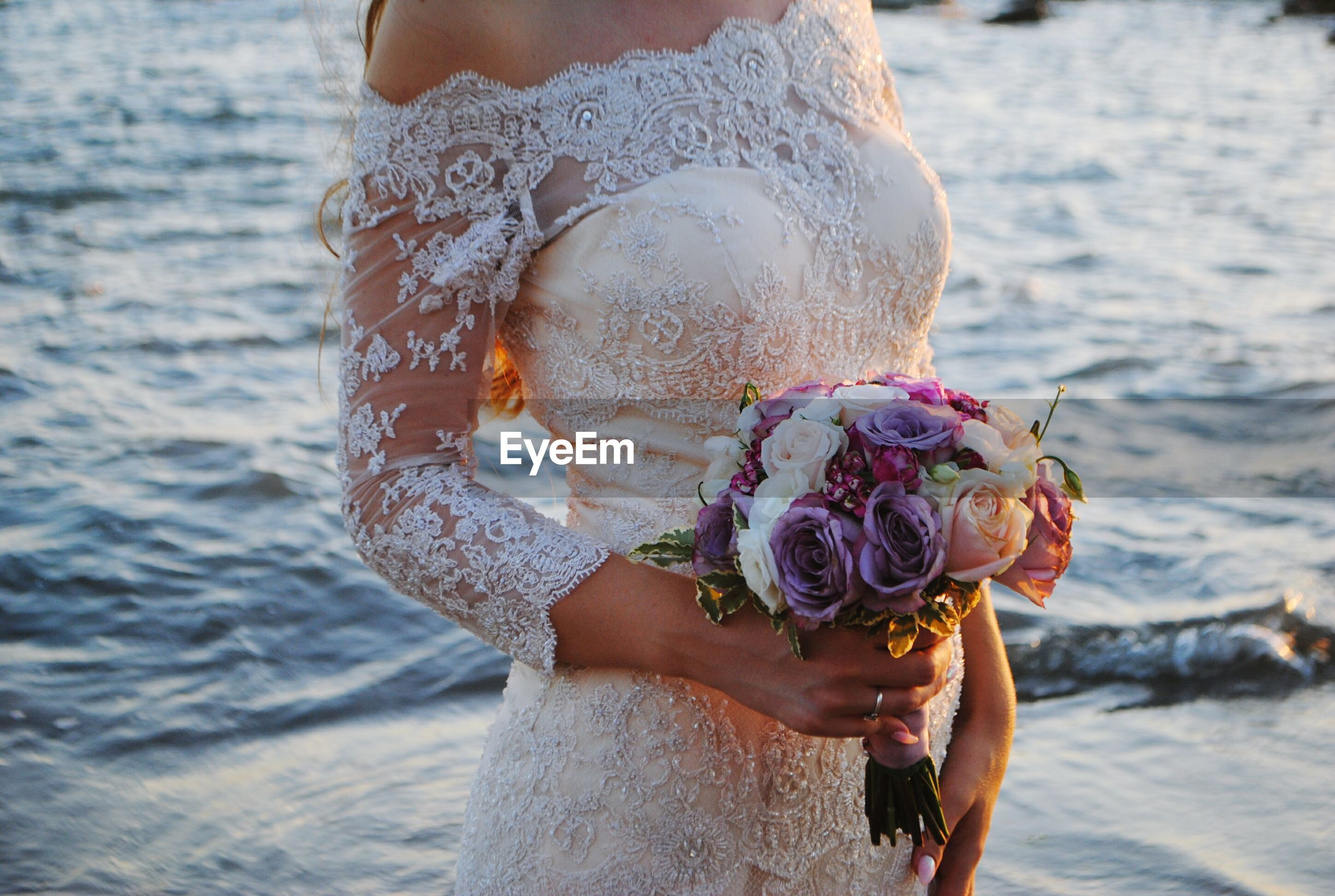 Close-up of bride holding flowers  while standing on beach