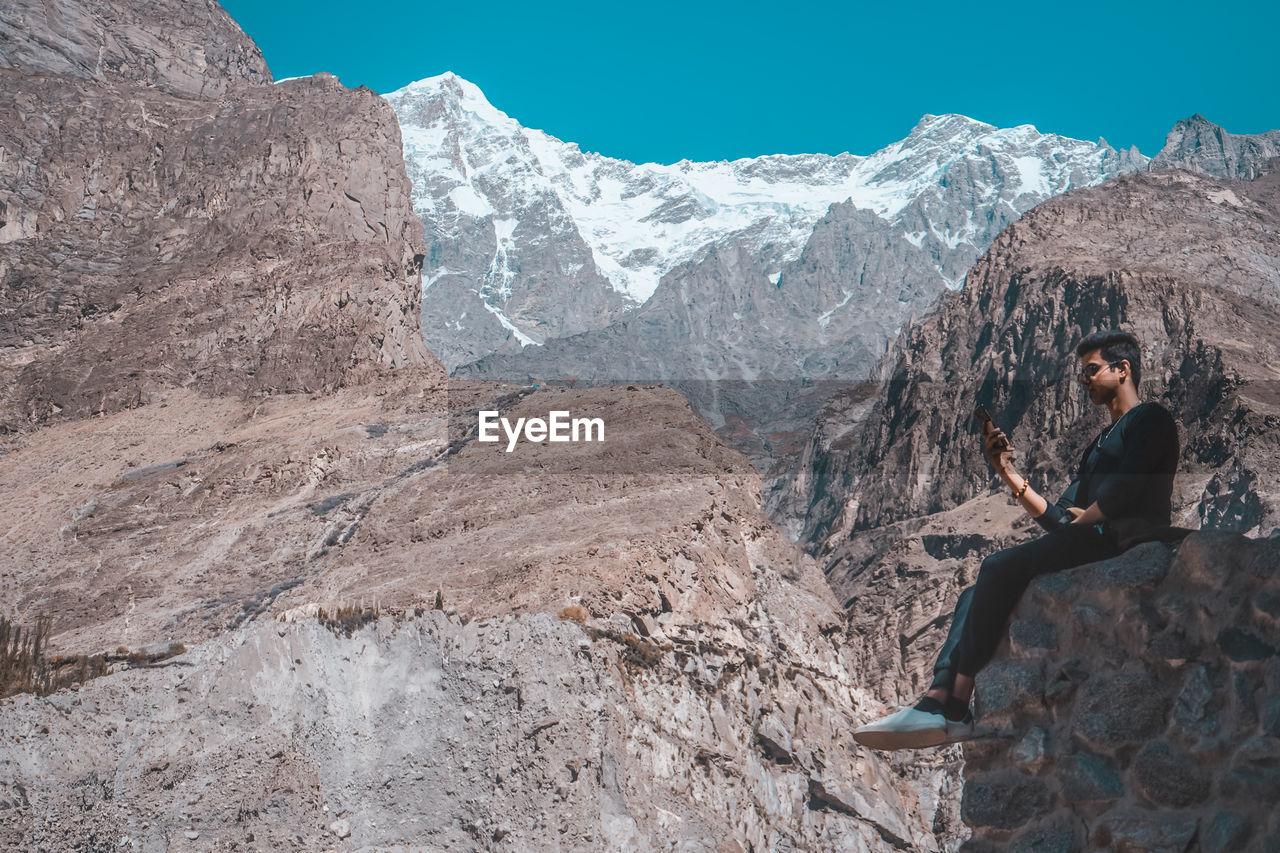 Man using phone while sitting on mountain