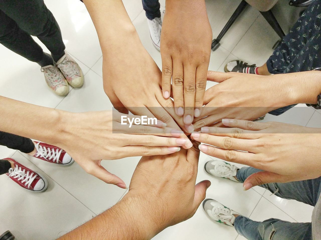 human hand, group of people, hand, human body part, cooperation, teamwork, real people, unity, togetherness, human finger, high angle view, indoors, finger, women, medium group of people, group, body part, bonding, personal perspective, adult, human limb
