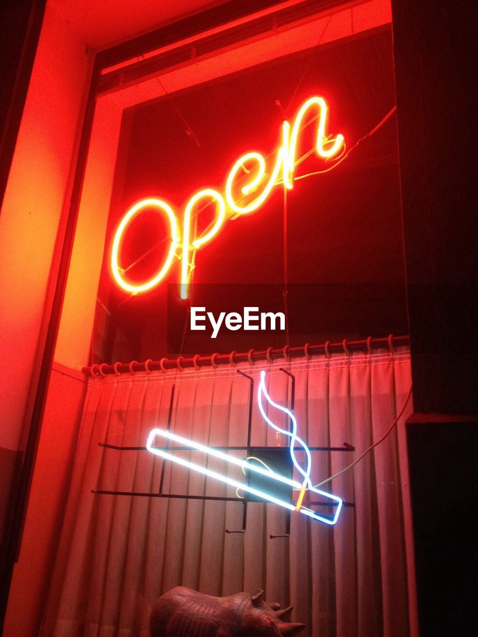 Low angle view of illuminated neon open sign on store window at night