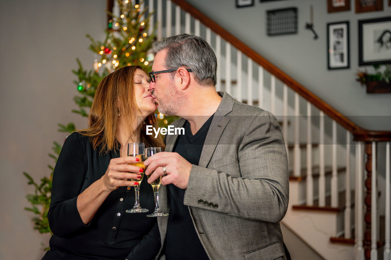 Man and woman kissing while toasting glasses