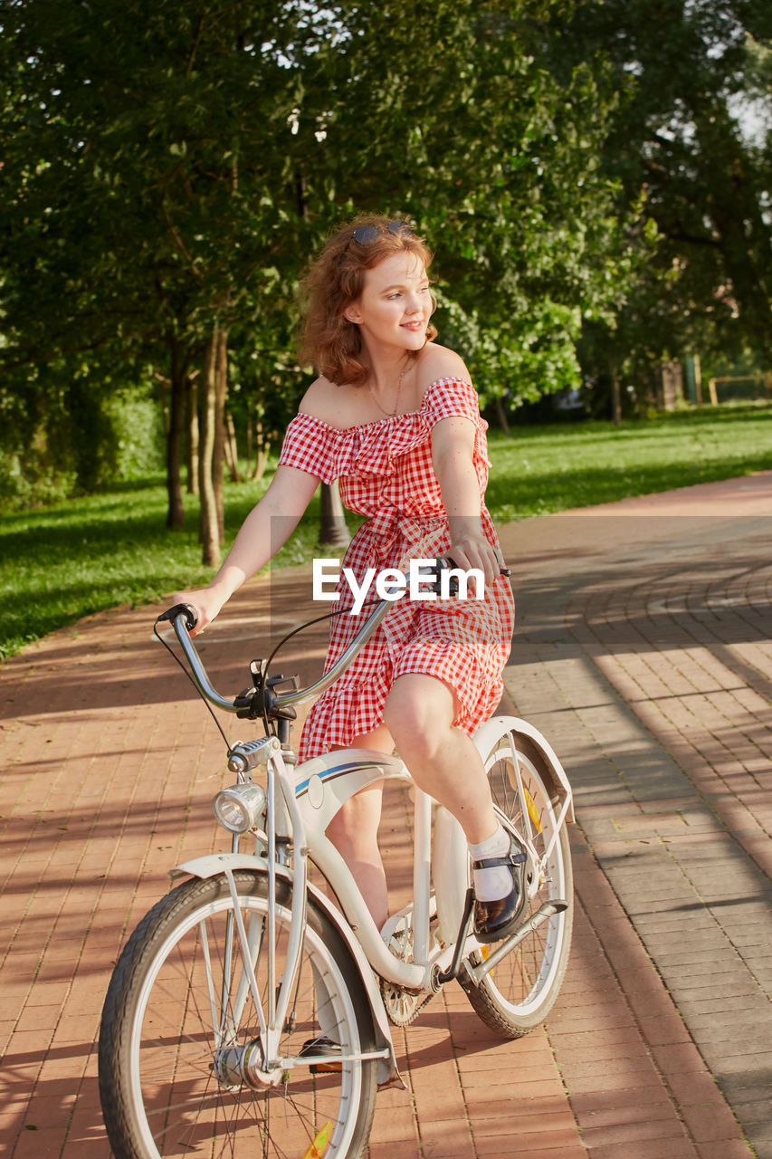 PORTRAIT OF SMILING WOMAN RIDING BICYCLE ON TREE
