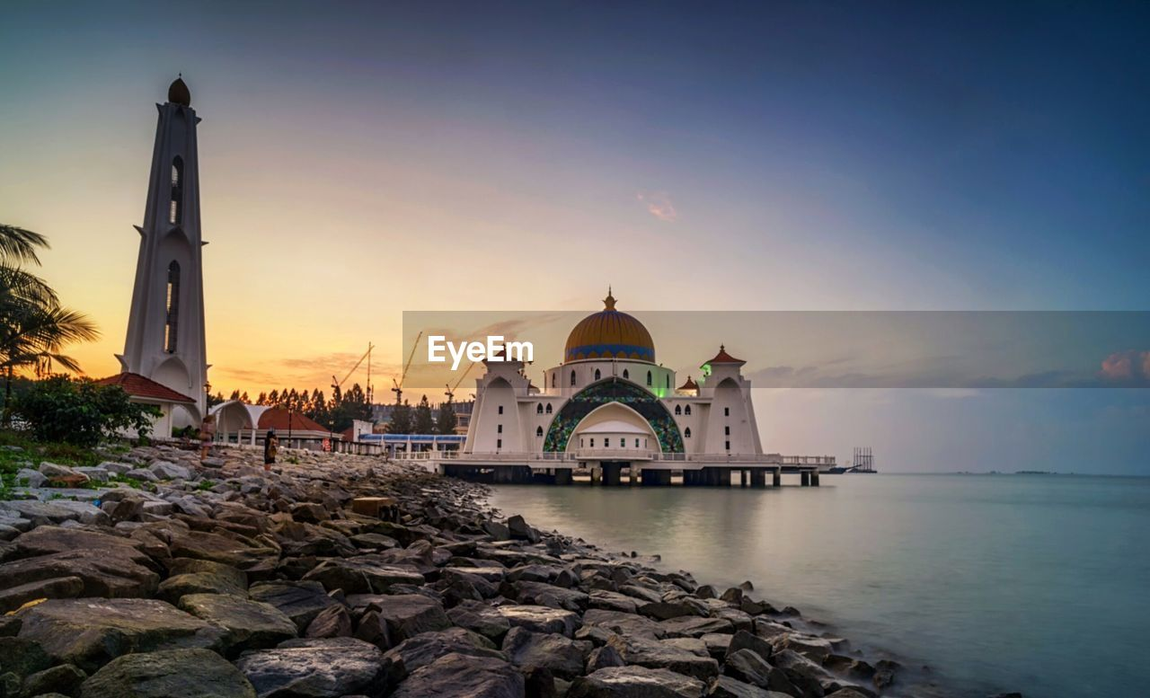 architecture, built structure, religion, sky, place of worship, belief, spirituality, building exterior, water, building, dome, sunset, rock, nature, travel destinations, rock - object, no people