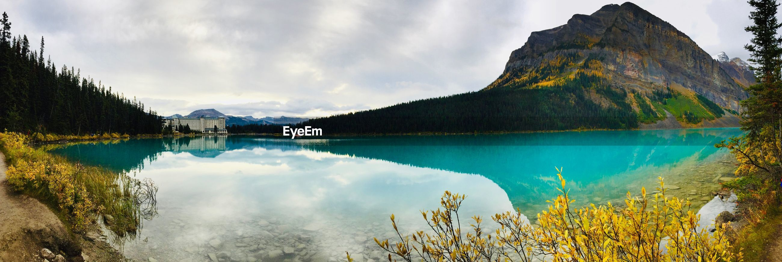 PANORAMIC VIEW OF LAKE AMIDST MOUNTAINS AGAINST SKY