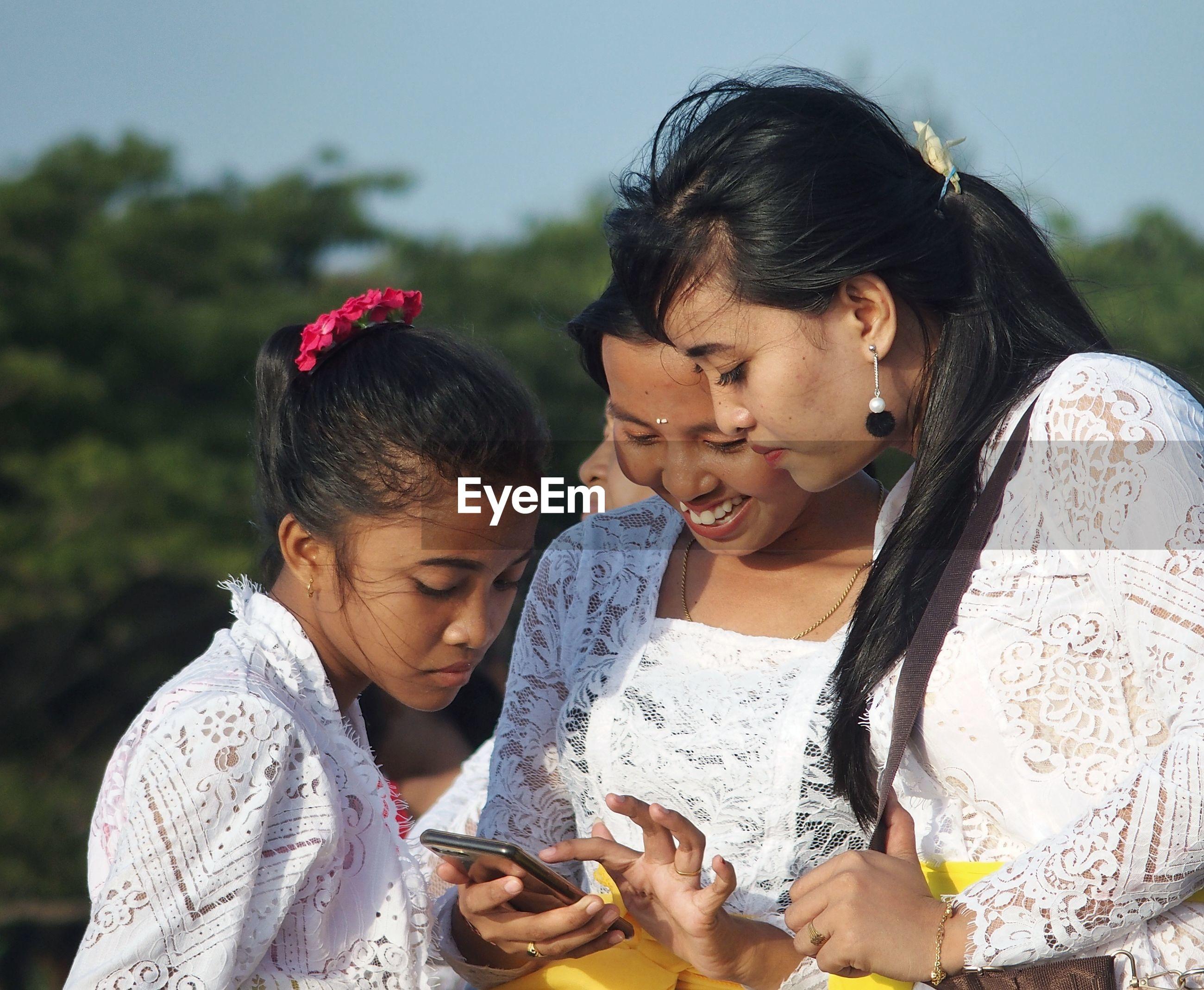 HAPPY WOMAN USING SMART PHONE AT CAMERA
