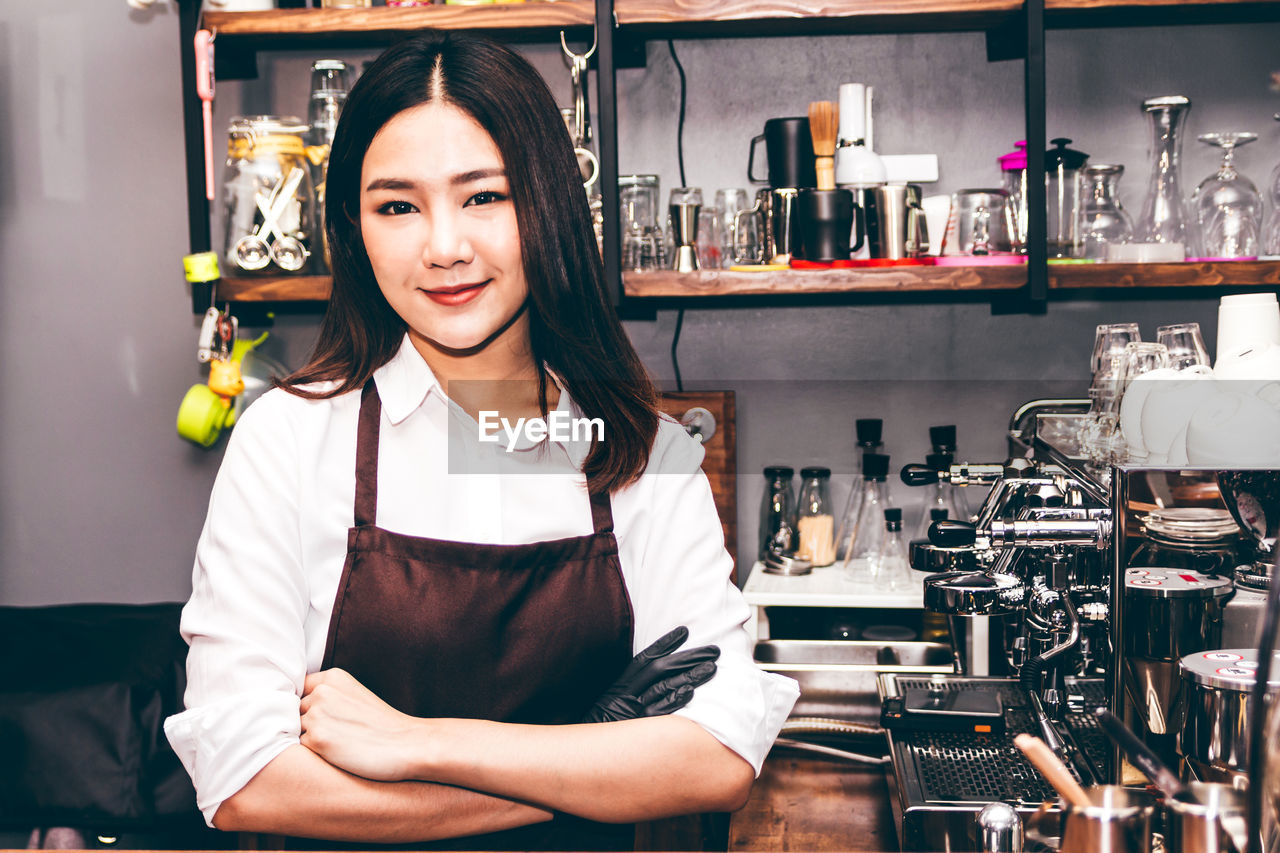 Portrait Of Female Barista With Arms Crossed Standing In Kitchen At Cafe