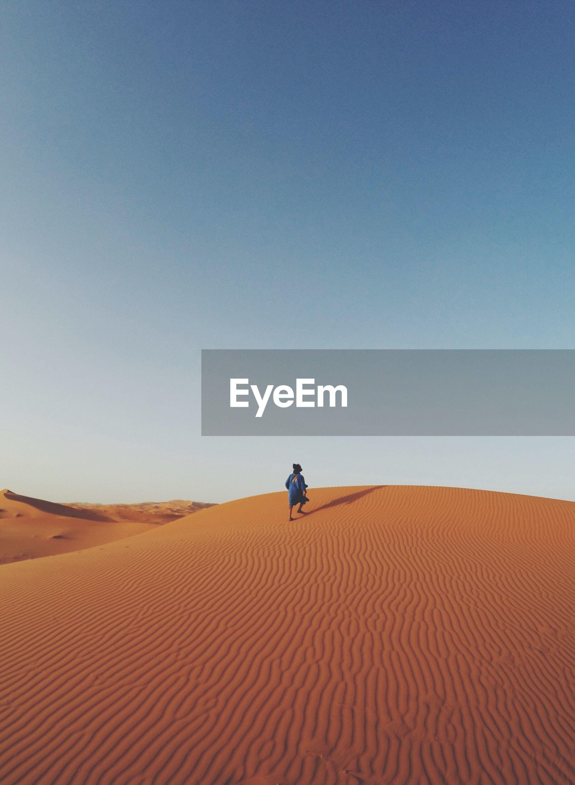 Man walking in desert against clear blue sky