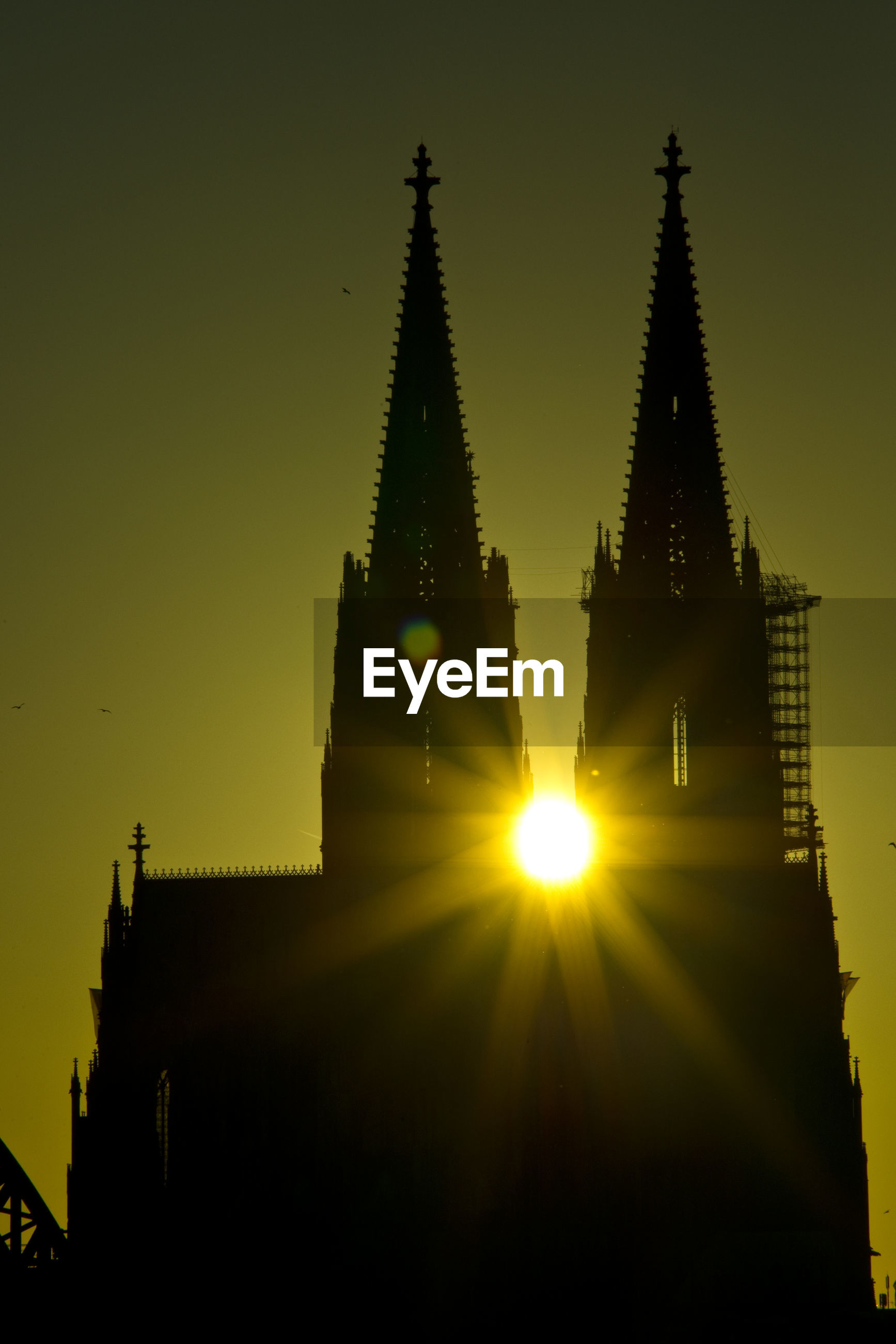 Low angle view of sunlight streaming through church against sky during sunset