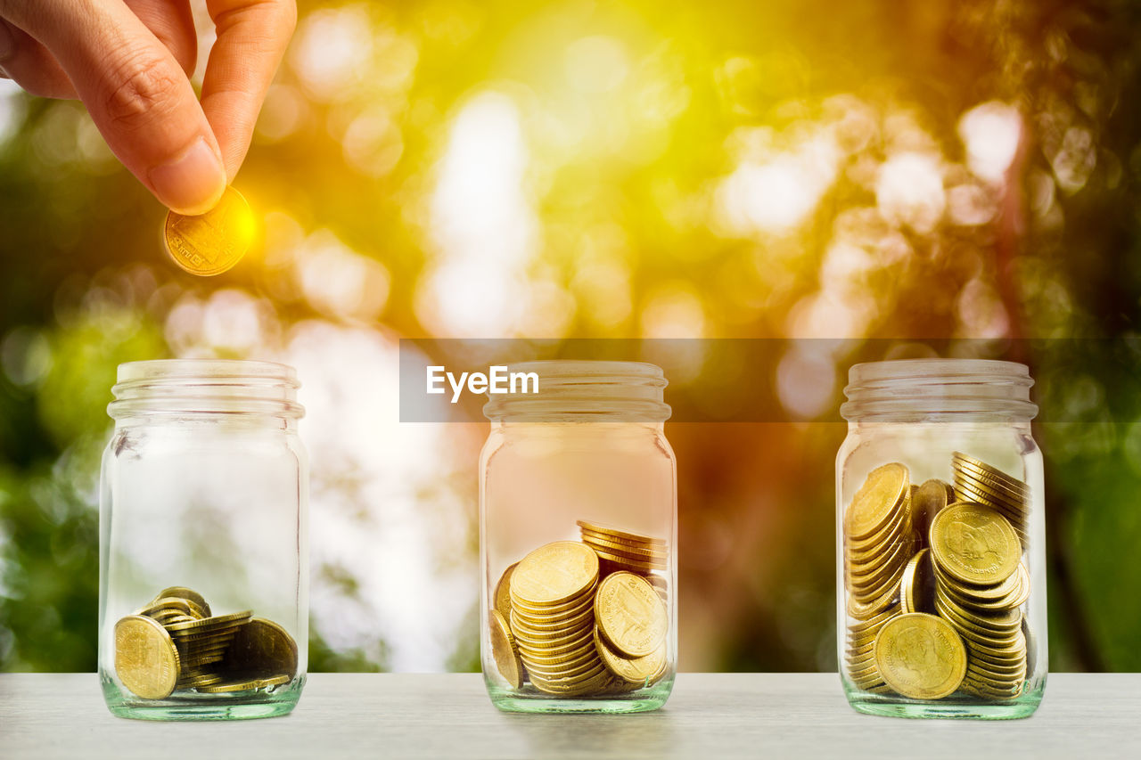 jar, coin, container, savings, finance, wealth, glass - material, focus on foreground, business, table, human hand, investment, currency, transparent, close-up, large group of objects, real people, human body part, hand, abundance, finger