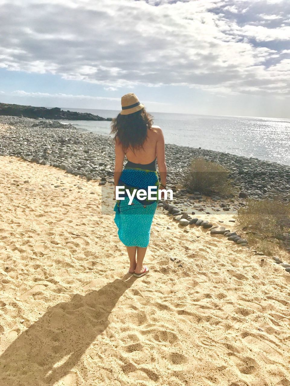 rear view, beach, sea, sand, full length, one person, real people, sky, nature, walking, leisure activity, horizon over water, sunlight, day, scenics, standing, water, lifestyles, vacations, women, beauty in nature, outdoors, adult, people