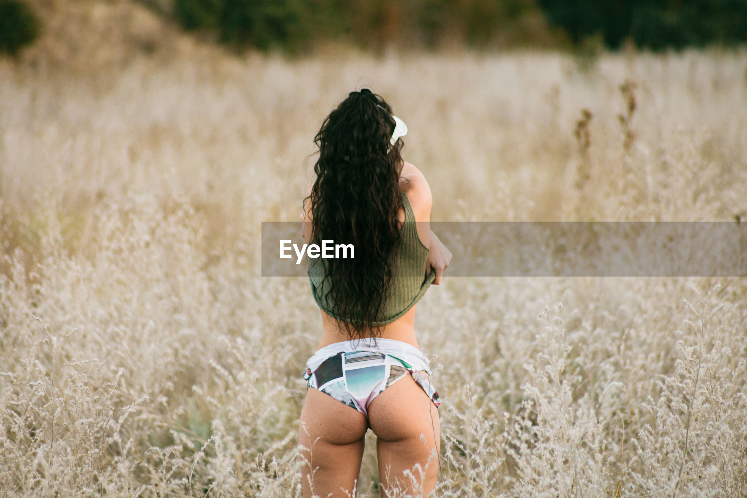 Rear view of young woman undressing while standing on grassy field