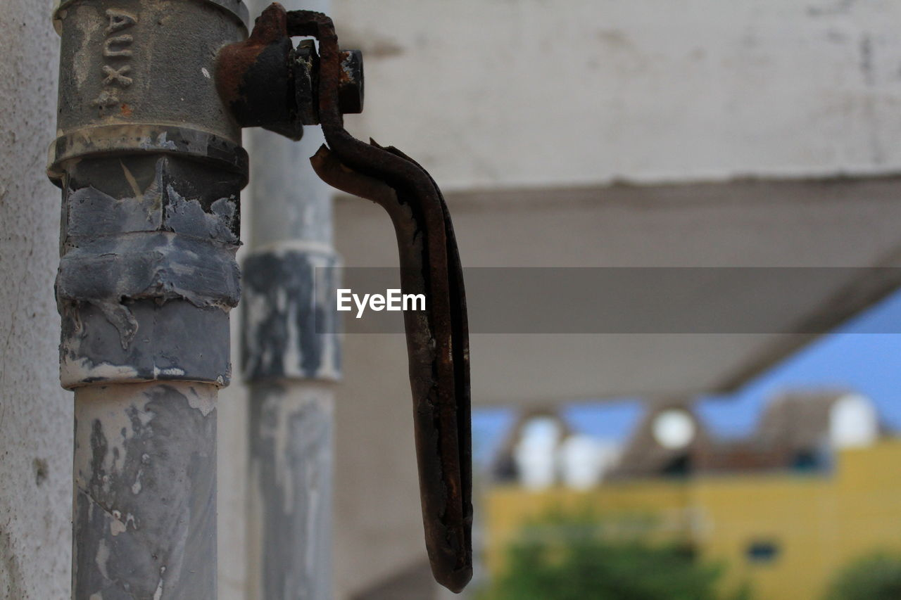 Close-up of old rusty pipe against wall