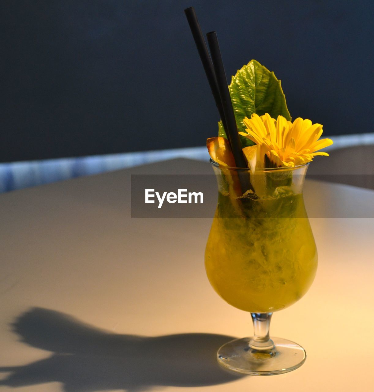 freshness, glass, table, alcohol, drink, close-up, household equipment, refreshment, drinking glass, still life, food and drink, yellow, cocktail, no people, indoors, focus on foreground, glass - material, food, flower, fruit, flower head, garnish