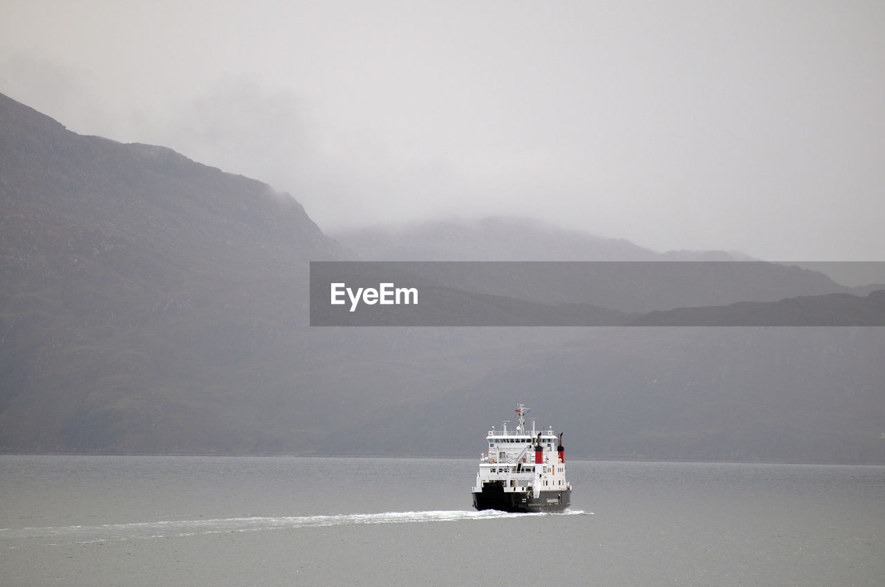 Boat In Sea With Mountain In Background