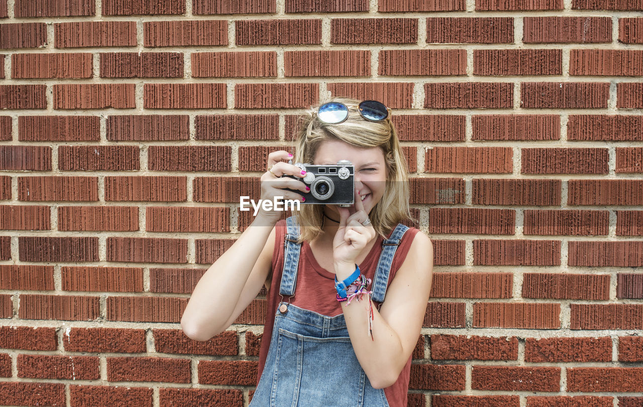 Portrait Of Young Woman Photographing Against Brick Wall