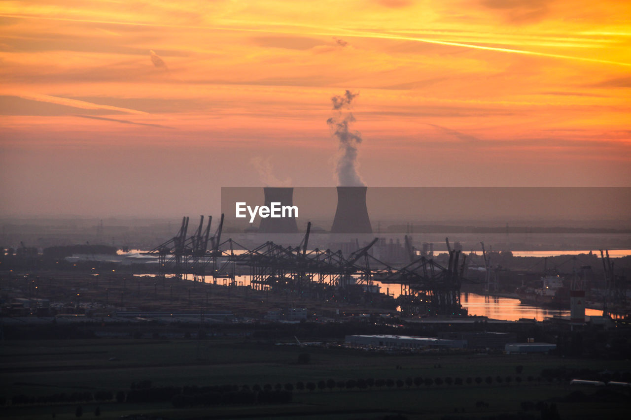 Smoke emitting from nuclear power plant at sunset