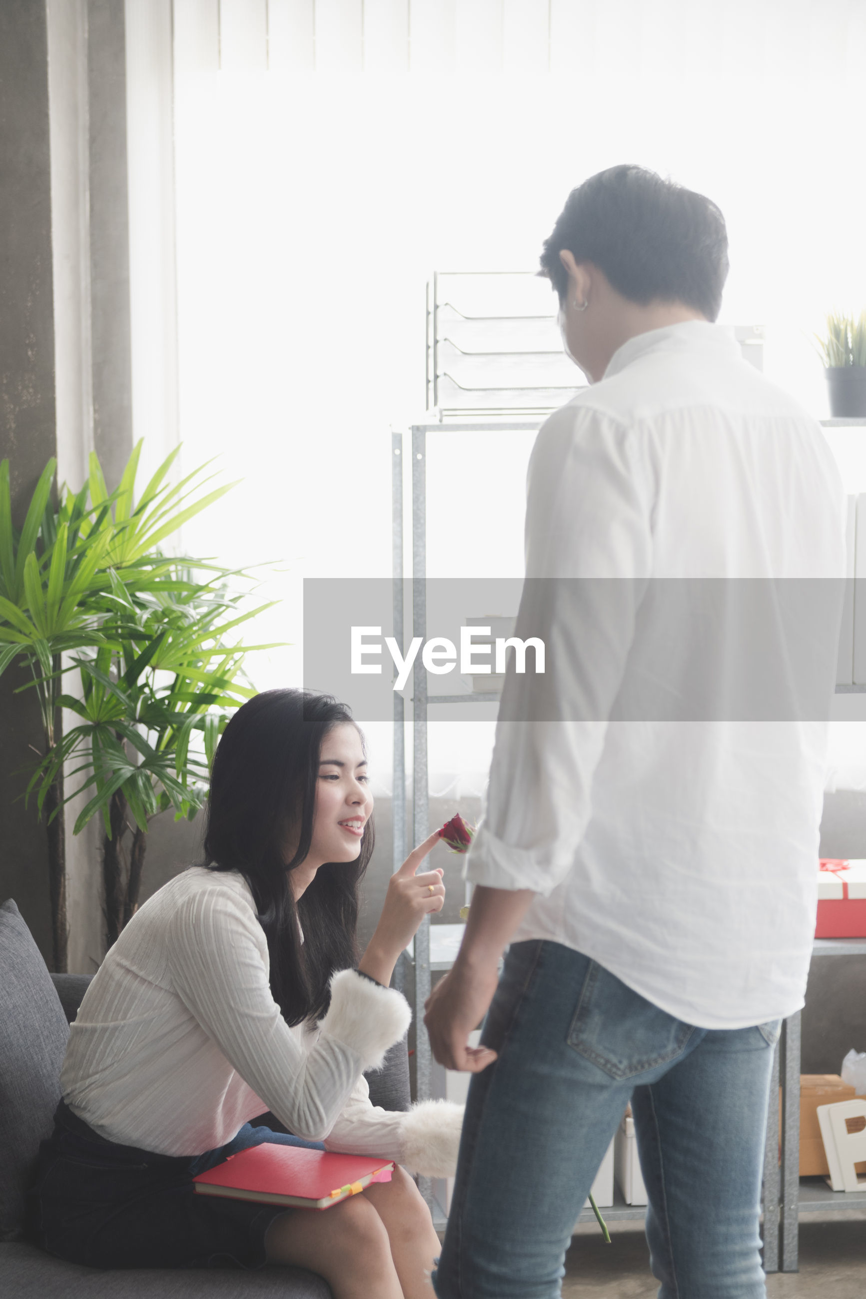 Man giving rose to woman at office
